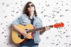 Forme el retrato de un adolescente que toca la guitarra en estudio mientras que lleva las gafas de sol y la chaqueta de los vaque Foto de archivo