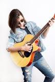 Forme el retrato de un adolescente que toca la guitarra en gafas de sol del estudio y chaqueta de los vaqueros que llevan Fotos de archivo