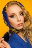 Forme el retrato de un blonde hermoso en un pañuelo y una a azules Fotografía de archivo