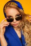 Forme el retrato de un blonde hermoso en una bufanda y un jacke azules Fotografía de archivo