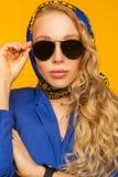 Forme el retrato de un blonde hermoso en una bufanda y un jacke azules foto de archivo libre de regalías