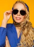 Forme el retrato de un blonde hermoso en una bufanda y un jacke azules foto de archivo