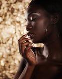 Forme el retrato del estudio de un modelo afroamericano hermoso extraordinario con los ojos cerrados sobre fondo de oro imágenes de archivo libres de regalías
