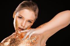 Forme el retrato del modelo rubio con la hoja de cobre en su cara, n Imagenes de archivo