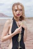 Forme el tiro de la muchacha rubia atractiva hermosa en bañador negro con un maquillaje brillante en un fondo de montañas en pust foto de archivo