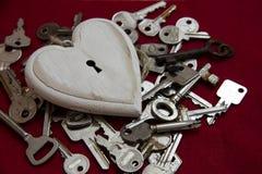 Forme en bois blanche de coeur avec un trou de la serrure sur beaucoup de clés, mais aucun Photos stock