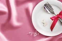 forme en bois de coeur avec le plat vide blanc avec la fourchette et la cuillère dessus Photographie stock libre de droits
