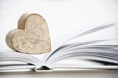 Forme en bois de coeur sur un livre ouvert Fin de concept de lecture d'amour  Photos libres de droits