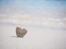 Forme en pierre de coeur se tenant sur le sable de plage d'été Photos stock