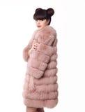 Forme a estudio el estilo adolescente de la mirada en el abrigo de pieles rosado aislado en pizca Fotografía de archivo