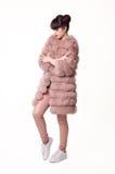 Forme a estudio el estilo adolescente de la mirada en abrigo de pieles rosado y zapatos de moda Imagen de archivo