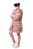 Forme a estudio el estilo adolescente de la mirada en abrigo de pieles rosado y zapatos de moda Fotos de archivo