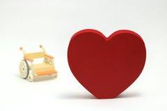 Forme et fauteuil roulant de coeur sur le fond blanc Photographie stock libre de droits
