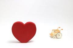 Forme et fauteuil roulant de coeur sur le fond blanc Images stock