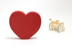 Forme et fauteuil roulant de coeur sur le fond blanc Photos libres de droits
