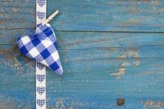 Forme faite main de coeur contre la surface en bois bleue pour le Ca de salutation Images stock