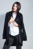 Forme a foto da jovem mulher em calças de brim na moda do preto do casaco de lã e Imagens de Stock
