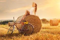 Forme a foto, mulher bonita que senta-se em um pacote do trigo, ao lado da bicicleta velha fotos de stock