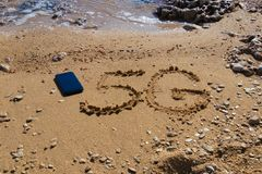 forme 5G sur le sable près du téléphone portable photos stock