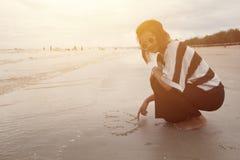 Forme heureuse de coeur d'aspiration de sourire de femmes d'Indy sur la plage Photographie stock
