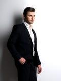 Forme a hombre joven en los asimientos blancos de la camisa la chaqueta negra Imagenes de archivo