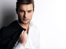 Forme a homem novo nas posses brancas da camisa o revestimento preto Fotografia de Stock Royalty Free