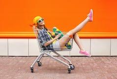 Forme a inconformista la muchacha fresca con el monopatín en carro de la compra Foto de archivo libre de regalías