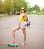 Forme a inconformista la muchacha fresca en gafas de sol con el monopatín Foto de archivo libre de regalías