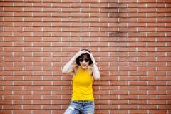 Forme a inconformista sonriente feliz la muchacha fresca en las gafas de sol que presentan en Imagen de archivo