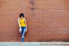 Forme a inconformista sonriente feliz la muchacha fresca en las gafas de sol que presentan en la pared de ladrillo Fotografía de archivo libre de regalías