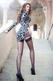 Forme a jovem mulher bonita com os pés longos que escalam escadas de pedra velhas. Morena longa bonita do cabelo no vestido curto  Fotografia de Stock