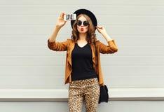 Forme a jovem mulher bonita o autorretrato de tomada modelo da imagem da foto no smartphone que veste o chapéu elegante retro, óc fotografia de stock royalty free