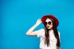 Forme a jovem mulher bonita que funde óculos de sol lipswearing vermelhos de um chapéu negro e o chapéu vermelho Imagens de Stock Royalty Free