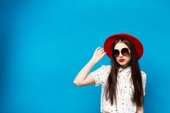 Forme a jovem mulher bonita que funde óculos de sol lipswearing vermelhos de um chapéu negro e o chapéu vermelho Foto de Stock Royalty Free