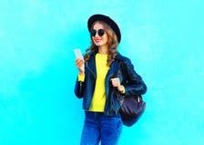 Forme a jovem mulher bonita que usa o smartphone roupa vestindo de um estilo da rocha do preto sobre o azul colorido Fotos de Stock Royalty Free