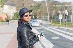 Forme a jovem mulher com telefone e os fones de ouvido espertos na rua, conceito urbano do estilo de vida Imagens de Stock Royalty Free