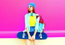 Forme a jovem mulher com um skate na cidade em um rosa imagens de stock royalty free