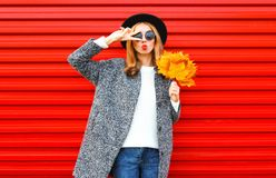 Forme a jovem mulher do outono com bordos vermelhos e as folhas de bordo amarelas foto de stock