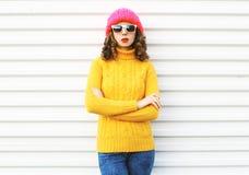 Forme a jovem mulher que veste o chapéu cor-de-rosa feito malha, camiseta colorida amarela sobre o branco Imagem de Stock Royalty Free