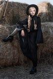 Forme a jovem mulher que veste o vestido e o chapéu pretos à moda no campo Estilo da forma de Amish fotografia de stock