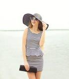 Forme a jovem mulher que veste um chapéu listrado do vestido e de palha foto de stock