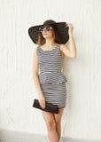 Forme a jovem mulher que veste um chapéu listrado do vestido e de palha fotografia de stock royalty free
