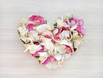 Forme l?g?re de coeur des p?tales de rose et blancs de rose et d'orchid?e sur le fond en bois Concept d'amour et de romance images libres de droits