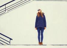 Forme la chaqueta que lleva y el sombrero de la mujer bastante rubia que presentan en ciudad del invierno sobre la pared blanca Fotos de archivo libres de regalías