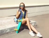 Forme a la chica joven bonita con el monopatín y la mochila al aire libre Imagenes de archivo