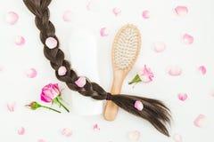 Forme la composición con el peine para diseñar del pelo, el champú y las flores rosadas en el fondo blanco Endecha plana, visión  Fotografía de archivo libre de regalías