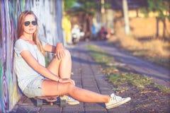 Forme la forma de vida, mujer rubia joven hermosa con el monopatín Fotos de archivo