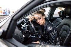 Forme la foto al aire libre de la mujer hermosa atractiva con el pelo oscuro en chaqueta de cuero negra y las gafas de sol que pr Imagen de archivo libre de regalías