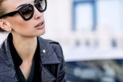 Forme la foto al aire libre de la mujer hermosa atractiva con el pelo oscuro en chaqueta de cuero negra y las gafas de sol que pr Imagenes de archivo