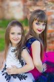 Forme la foto de dos muchachas hermosas en un fondo del ladrillo ru Foto de archivo libre de regalías